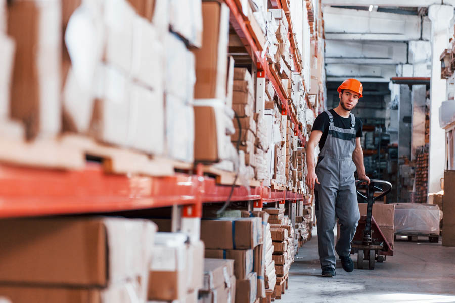 Business Industry Specialties - Man Walking with Cart in a Warehouse